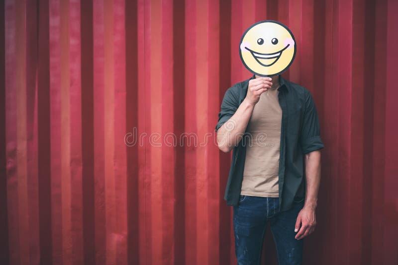 Νεαρός άνδρας που φαίνεται αστείος στεμένος με την εικόνα χαμόγελου στοκ φωτογραφίες