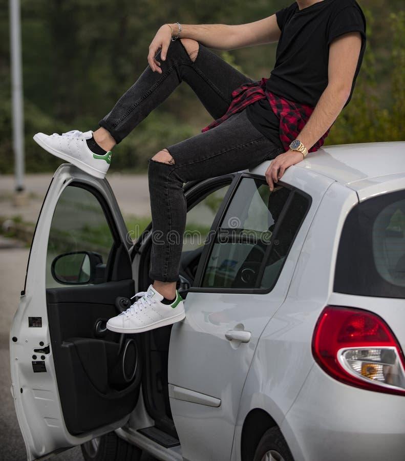 Νεαρός άνδρας που φοράει παπούτσια Adidas Stan Smith και κάθεται σε ένα λευκό αυτοκίνητο στοκ εικόνες με δικαίωμα ελεύθερης χρήσης