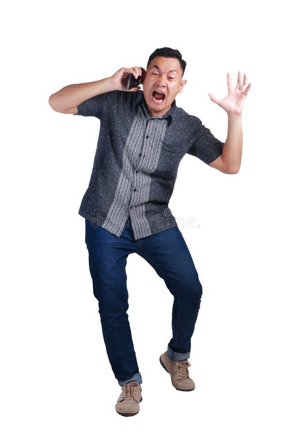 Νεαρός άνδρας που φωνάζει στο τηλέφωνό του, η έκφραση στοκ εικόνα