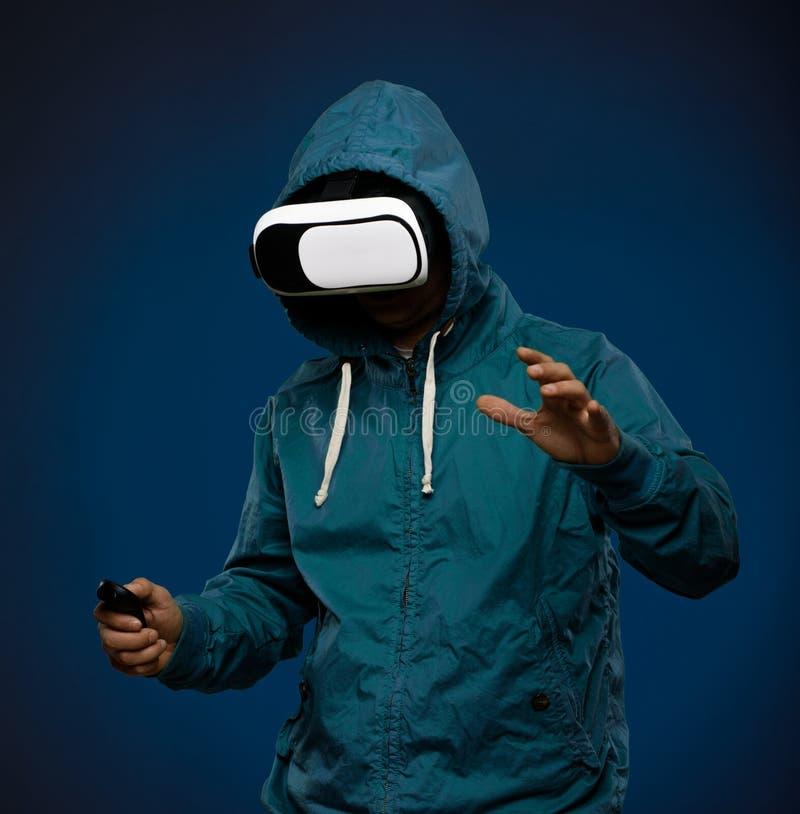 Νεαρός άνδρας που χρησιμοποιεί τα γυαλιά VR κασκών Άτομο με την εικονική πραγματικότητα γ στοκ εικόνες