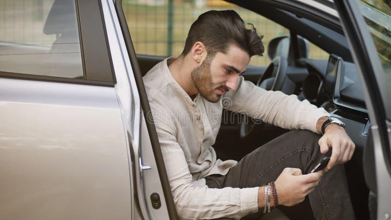 Νεαρός άνδρας που χρησιμοποιεί την κινητή τηλεφωνική συνεδρίαση στο αυτοκίνητο στοκ εικόνες