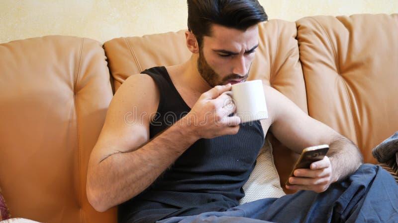 Νεαρός άνδρας που χρησιμοποιεί το τηλέφωνο κυττάρων πίνοντας τον καφέ στοκ εικόνες με δικαίωμα ελεύθερης χρήσης