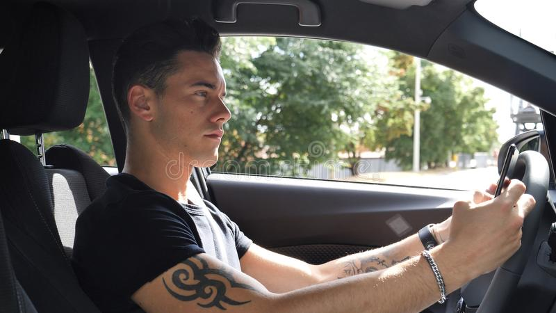 Νεαρός άνδρας που χρησιμοποιεί το τηλεφωνικό Drive αυτοκίνητο κυττάρων του στοκ εικόνα