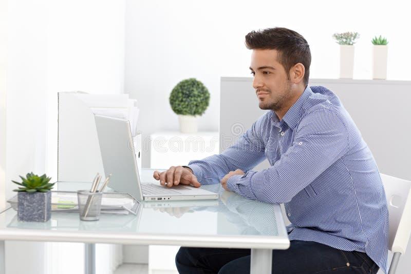 Νεαρός άνδρας που χρησιμοποιεί το φορητό προσωπικό υπολογιστή στοκ φωτογραφία με δικαίωμα ελεύθερης χρήσης