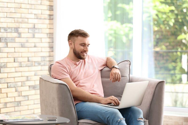 Νεαρός άνδρας που χρησιμοποιεί το lap-top καθμένος στην πολυθρόνα στοκ εικόνα