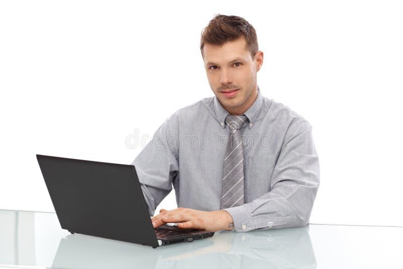 Νεαρός άνδρας που χρησιμοποιεί το lap-top στοκ φωτογραφία