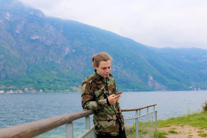 Νεαρός άνδρας που χρησιμοποιεί το smartphone κοντά στη ράμπα, τη λίμνη Como και το βουνό Άλπεων στο υπόβαθρο στοκ εικόνες