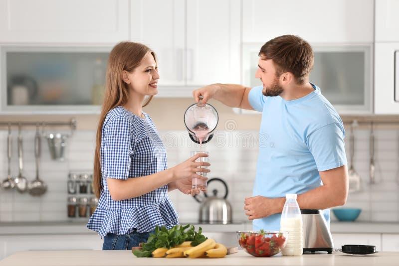 Νεαρός άνδρας που χύνει το εύγευστο κούνημα γάλακτος στο γυαλί στην κουζίνα στοκ εικόνα με δικαίωμα ελεύθερης χρήσης