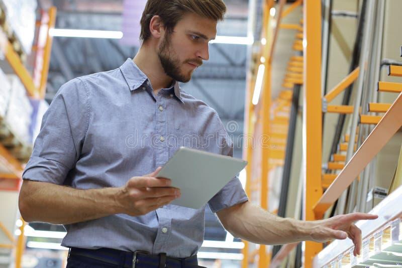 Νεαρός άνδρας που ψωνίζει ή που εργάζεται σε μια αποθήκη εμπορευμάτων υλικού που στέκεται ελέγχοντας τις προμήθειες στην ταμπλέτα στοκ φωτογραφίες