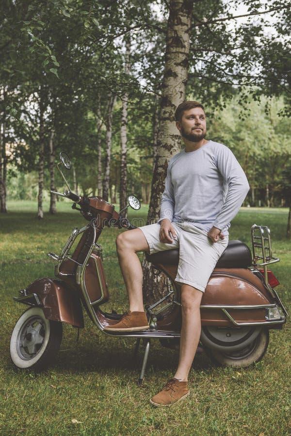 νεαρός άνδρας σε ένα εκλεκτής ποιότητας μηχανικό δίκυκλο στο πάρκο στοκ εικόνες