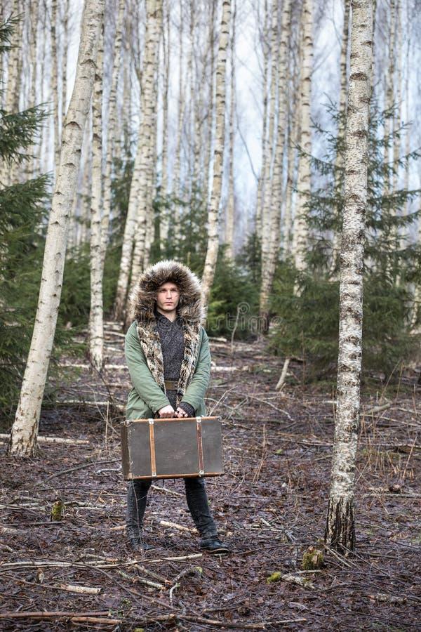 Νεαρός άνδρας σε μια πράσινη χειμερινή ζακέτα σε ένα δάσος με μια βαλίτσα στοκ φωτογραφίες με δικαίωμα ελεύθερης χρήσης