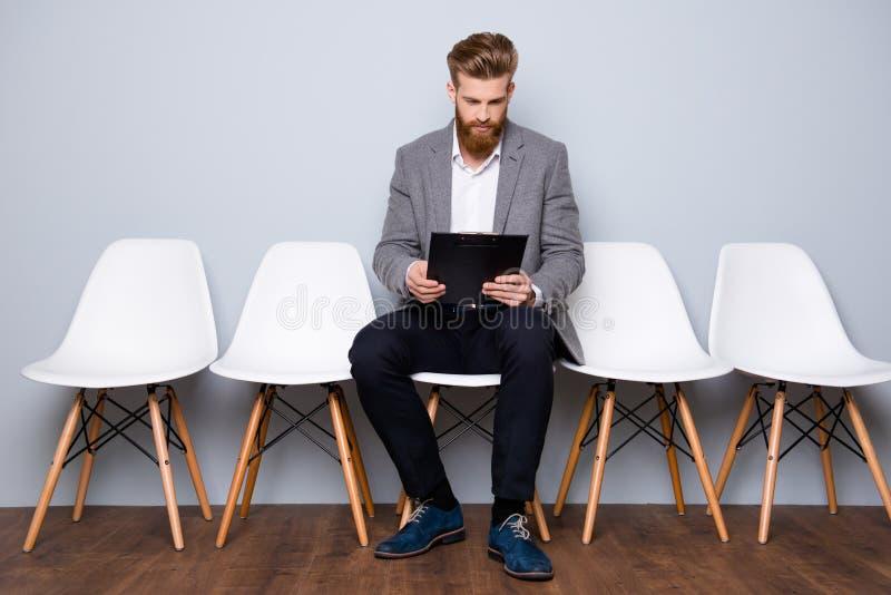 Νεαρός άνδρας σε formalwear με την κόκκινη περιοχή αποκομμάτων γενειάδων holdyng με το βιογραφικό σημείωμα στοκ εικόνες