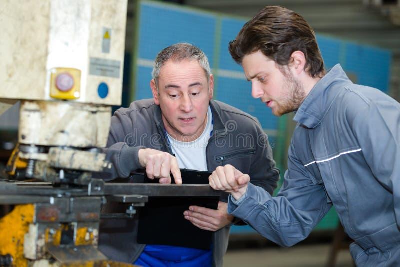 Νεαρός άνδρας στα σιδηρουργεία που εκπαιδεύει με τον επαγγελματικό δάσκαλο στοκ φωτογραφία