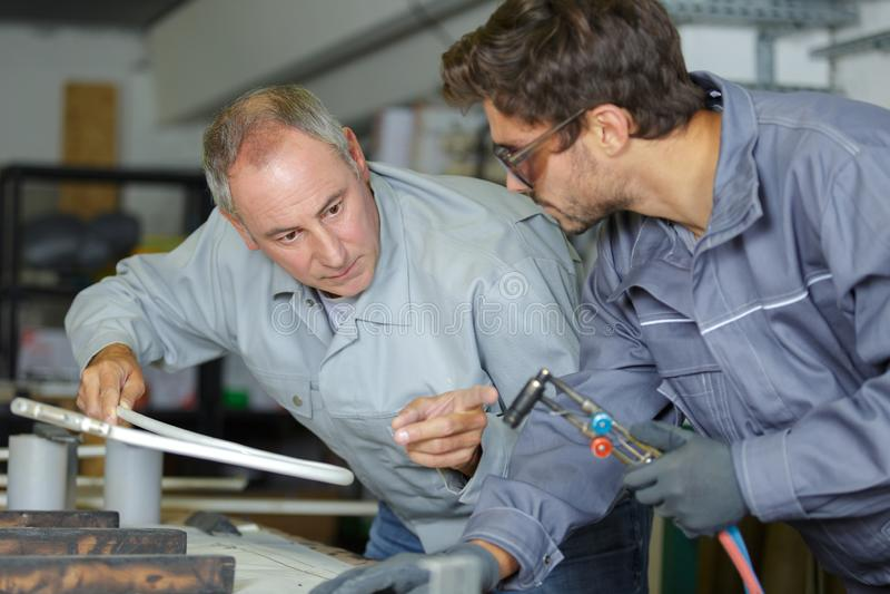 Νεαρός άνδρας στα σιδηρουργεία που εκπαιδεύει με τον επαγγελματικό δάσκαλο στοκ εικόνες