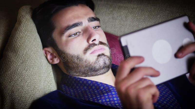 Νεαρός άνδρας στην ανάγνωση καναπέδων με το PC ταμπλετών στοκ εικόνα με δικαίωμα ελεύθερης χρήσης