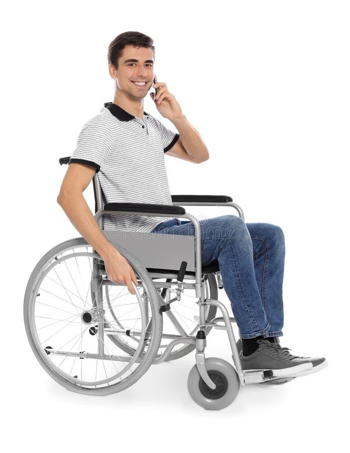 Νεαρός άνδρας στην αναπηρική καρέκλα ομιλία με κινητό τηλέφωνο που απομονώνεται στοκ φωτογραφίες