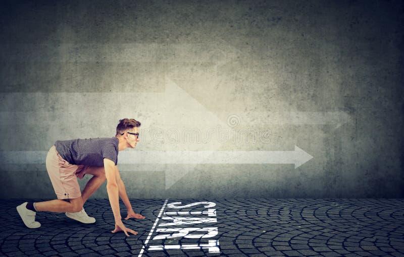 Νεαρός άνδρας στην αρχική θέση έτοιμη να τρέξει στοκ φωτογραφίες