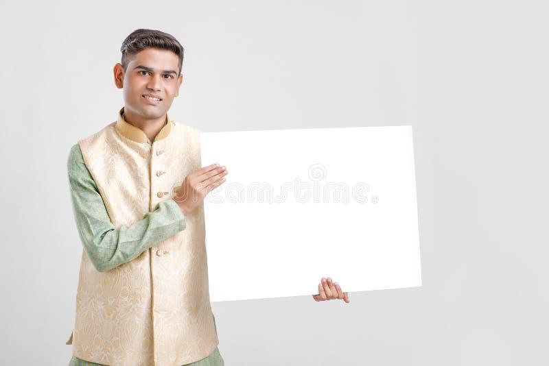 Νεαρός άνδρας στην εθνική ένδυση και την παρουσίαση κενού πίνακα σημαδιών στοκ φωτογραφίες
