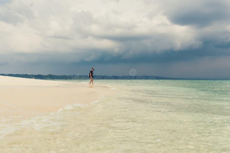 Νεαρός άνδρας στην όμορφη ηλιόλουστη άσπρη παραλία άμμου στοκ φωτογραφίες με δικαίωμα ελεύθερης χρήσης