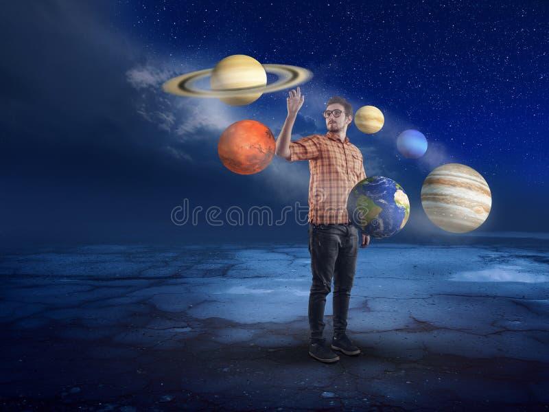 Νεαρός άνδρας στη μέση του ηλιακού συστήματος στοκ εικόνα
