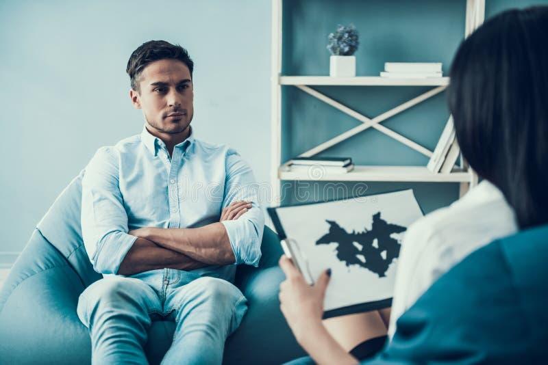 Νεαρός άνδρας στη συνάντηση με τη δοκιμή Rorschach ψυχολόγων στοκ φωτογραφίες