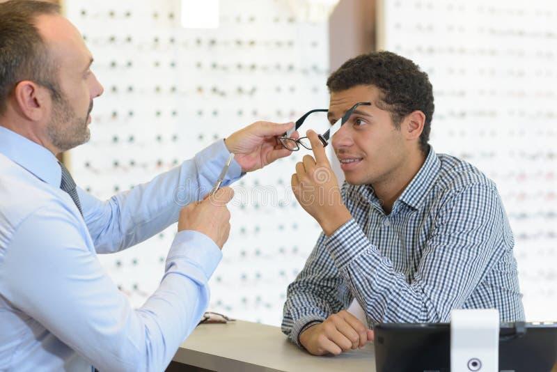 Νεαρός άνδρας στους οπτικούς που προσπαθούν στα γυαλιά στοκ εικόνες με δικαίωμα ελεύθερης χρήσης