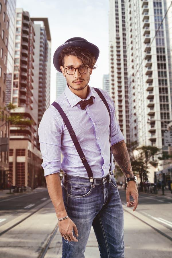 Νεαρός άνδρας στο καπέλο, τα γυαλιά, τον τόξο-δεσμό και suspenders που εξετάζει τη κάμερα στοκ φωτογραφίες