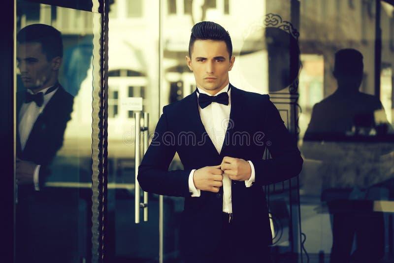 Νεαρός άνδρας στο κοστούμι κοντά στην πόρτα γυαλιού στοκ φωτογραφία