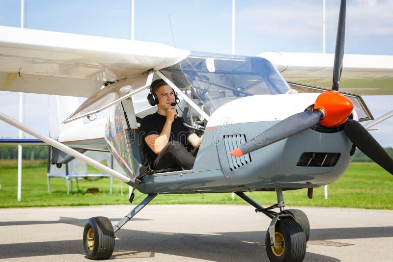Νεαρός άνδρας στο μικρό πιλοτήριο αεροπλάνων στοκ φωτογραφίες