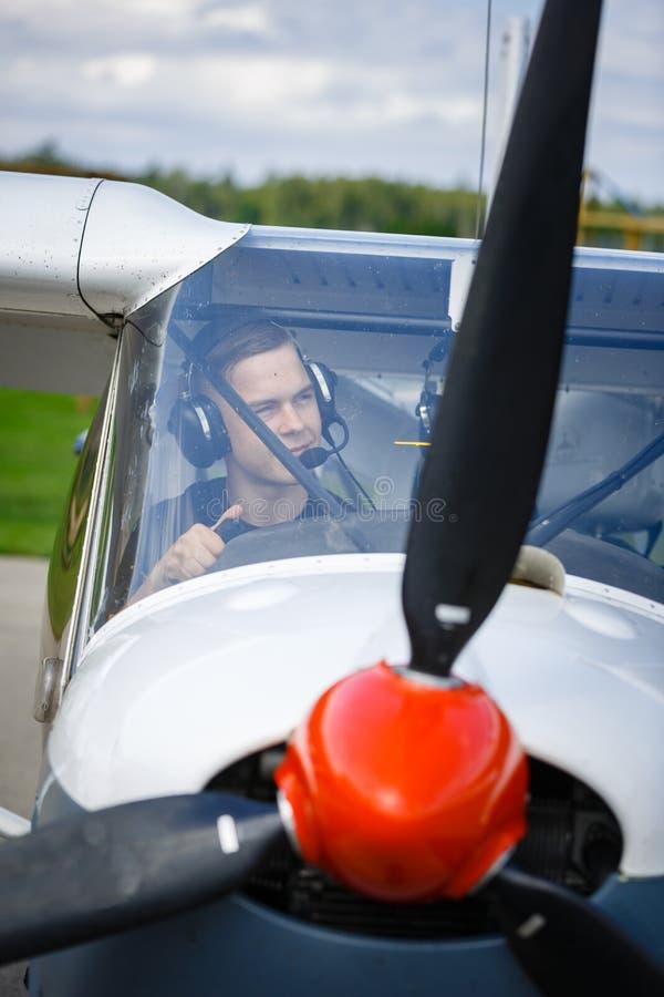 Νεαρός άνδρας στο μικρό πιλοτήριο αεροπλάνων στοκ φωτογραφία με δικαίωμα ελεύθερης χρήσης