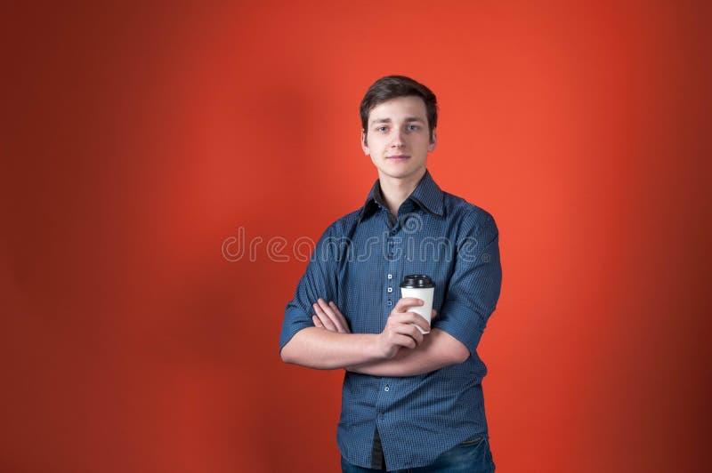 Νεαρός άνδρας στο μπλε πουκάμισο με τα διασχισμένα όπλα που εξετάζουν τη κάμερα και που κρατούν το φλυτζάνι εγγράφου με τον καφέ  στοκ εικόνα με δικαίωμα ελεύθερης χρήσης