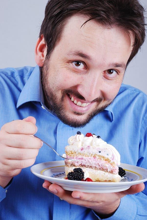 Νεαρός άνδρας το ζωηρόχρωμο κέικ, που απομονώνεται που τρώει στοκ φωτογραφία με δικαίωμα ελεύθερης χρήσης