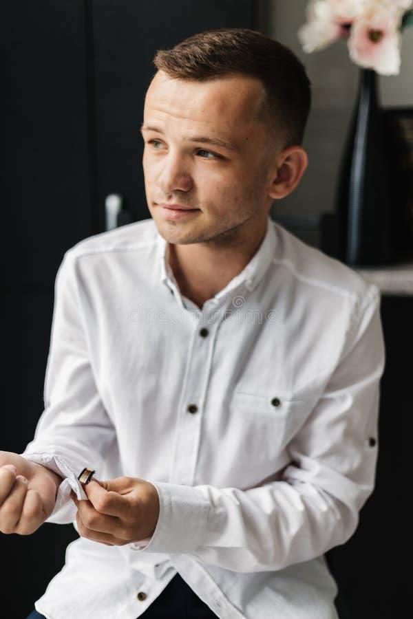 Νεαρός άνδρας φοράει πουκάμισο και κοιτάζει έξω από το παράθυρο στοκ φωτογραφία