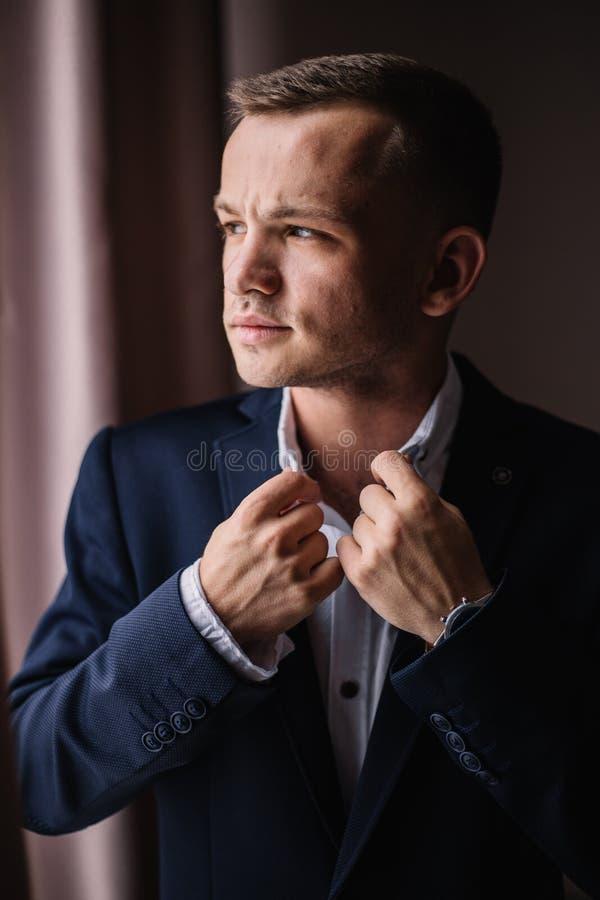 Νεαρός άνδρας φοράει πουκάμισο και κοστούμι Και κοιτάξτε έξω από το παράθυρο στοκ φωτογραφία με δικαίωμα ελεύθερης χρήσης