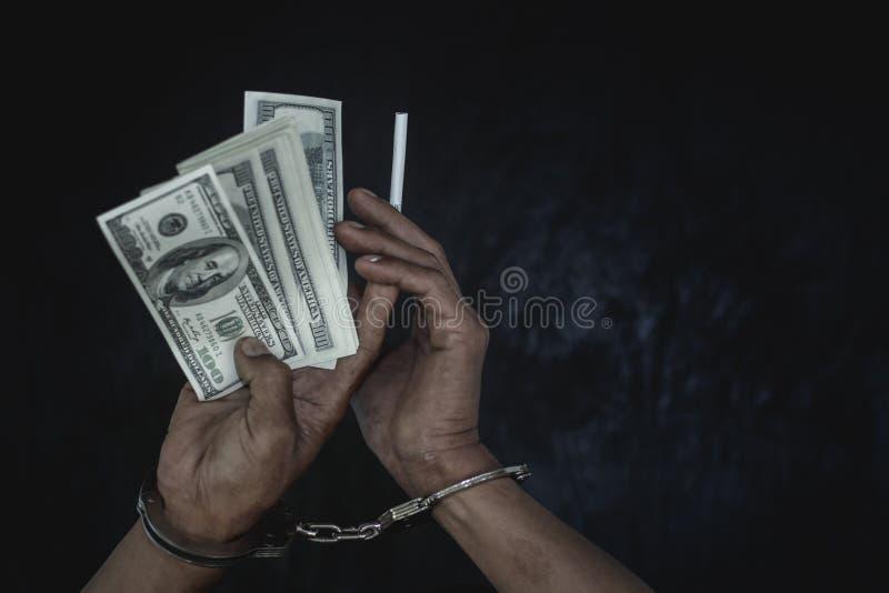 Νεαρός άνδρας χεριών στα δεμένα με χειροπέδες χρήματα λαβής, διανεμητής ναρκωτικών σύλληψης αστυνομίας με τις χειροπέδες Νόμος κα στοκ εικόνες