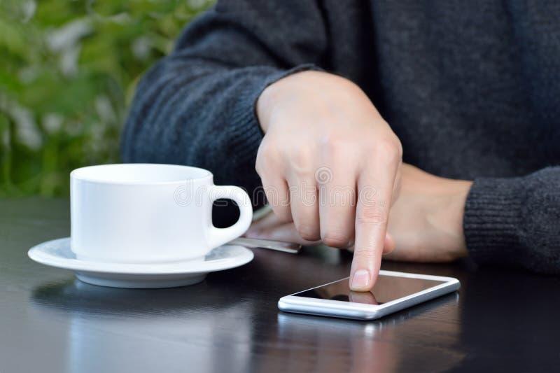 νεαρός άνδρας χρησιμοποιώντας ένα κινητό τηλέφωνο και πίνοντας έναν καφέ καθμένος σε έναν καφέ στοκ εικόνες με δικαίωμα ελεύθερης χρήσης