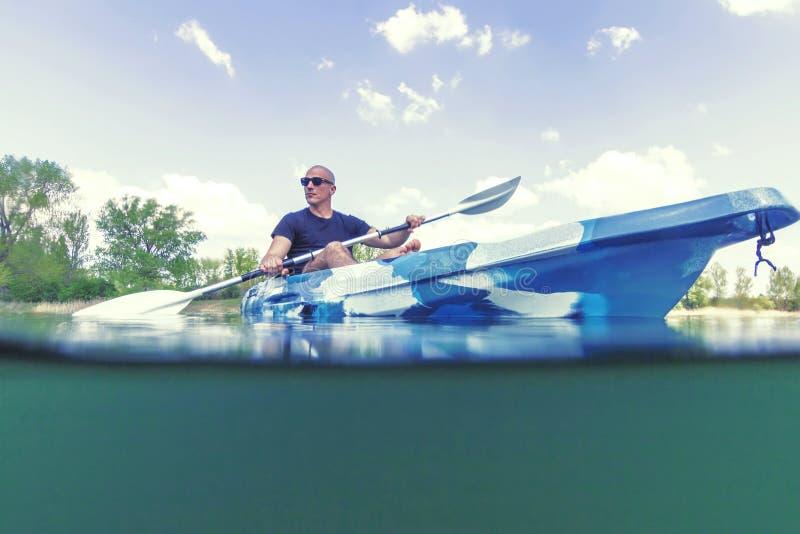 Νεαρός άνδρας Kayaking στη λίμνη, υποβρύχια άποψη Kayaking, διασπασμένος πυροβολισμός στοκ φωτογραφίες με δικαίωμα ελεύθερης χρήσης