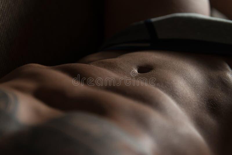 Νεαρός άνδρας δερματοστιξιών κινηματογραφήσεων σε πρώτο πλάνο που βάζει στο κρεβάτι στοκ εικόνες με δικαίωμα ελεύθερης χρήσης