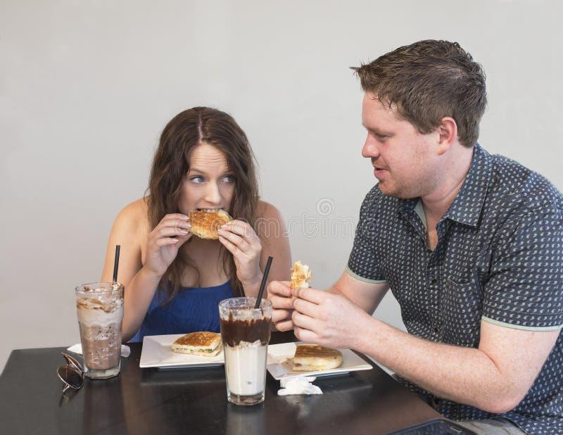 Νεαρός άνδρας και γυναίκα που κουβεντιάζουν τρώγοντας το μεσημεριανό γεύμα στοκ φωτογραφία με δικαίωμα ελεύθερης χρήσης