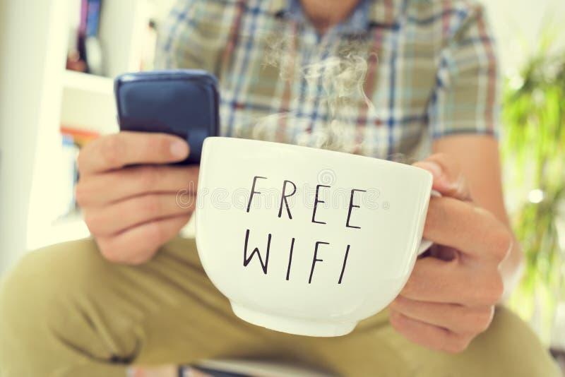 Νεαρός άνδρας με ένα smartphone και ένα φλιτζάνι του καφέ με το κείμενο FR στοκ εικόνες