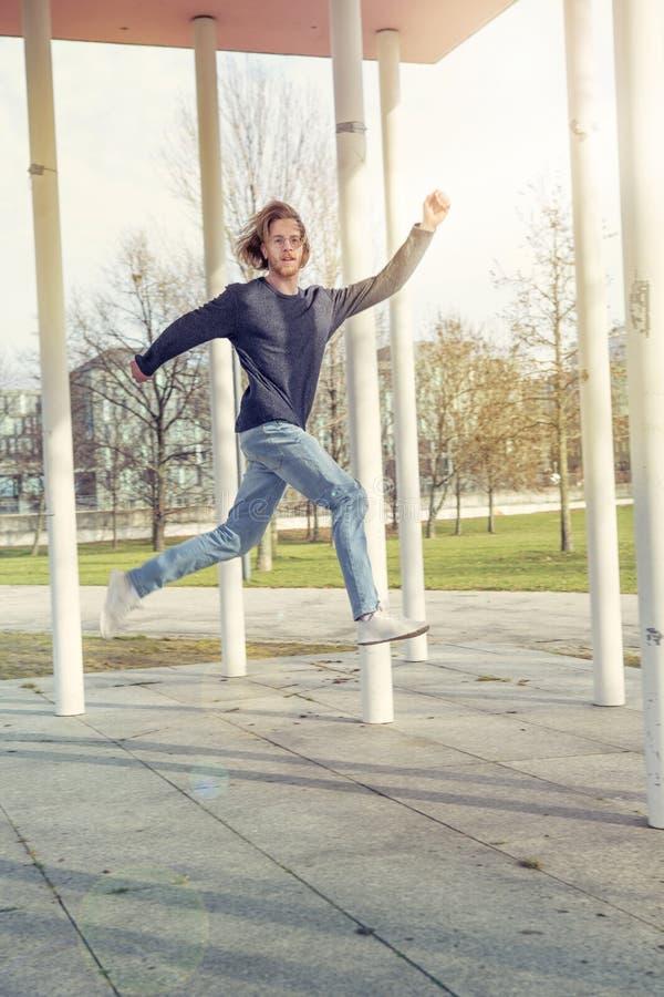 Νεαρός άνδρας με την κόκκινη τρίχα που πηδά έξω στοκ εικόνες με δικαίωμα ελεύθερης χρήσης