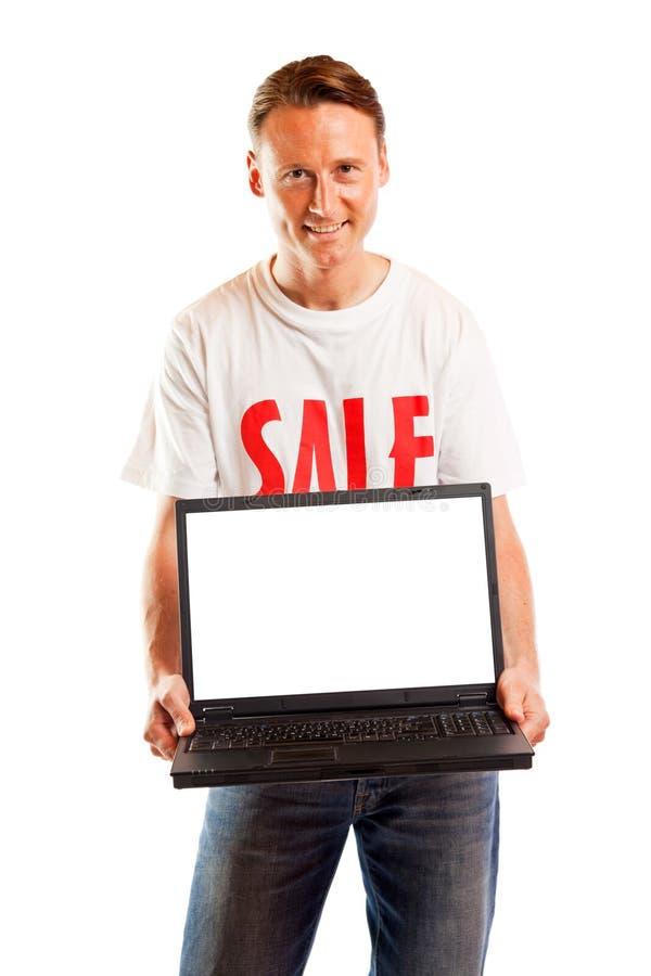 Νεαρός άνδρας με την μπλούζα και το lap-top πώλησης ` ` στοκ εικόνες