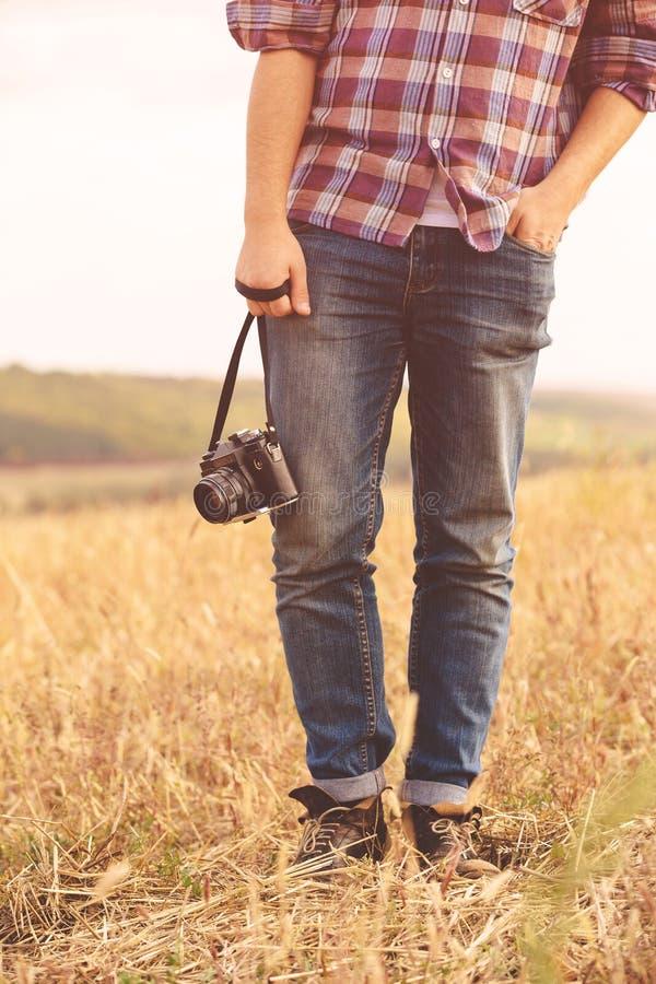 Νεαρός άνδρας με τον αναδρομικό φωτογραφιών τρόπο ζωής hipster καμερών υπαίθριο στοκ εικόνες