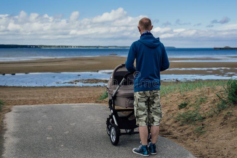 Νεαρός άνδρας με τον περιπατητή μωρών στην παραλία στοκ φωτογραφία με δικαίωμα ελεύθερης χρήσης