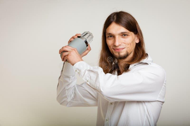 Νεαρός άνδρας με το δονητή που κατασκευάζει το ποτό κοκτέιλ στοκ φωτογραφία