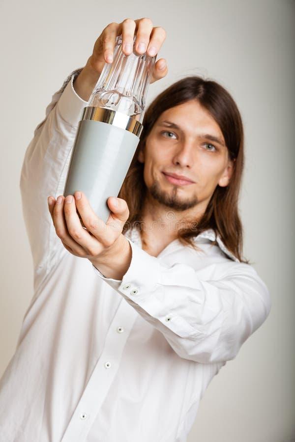 Νεαρός άνδρας με το δονητή που κατασκευάζει το ποτό κοκτέιλ στοκ εικόνα
