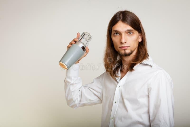 Νεαρός άνδρας με το δονητή που κατασκευάζει το ποτό κοκτέιλ στοκ εικόνα με δικαίωμα ελεύθερης χρήσης