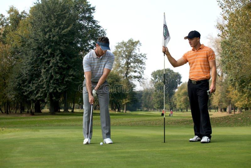 Νεαρός άνδρας με το παίζοντας γκολφ φίλων του στο γήπεδο του γκολφ στοκ εικόνα