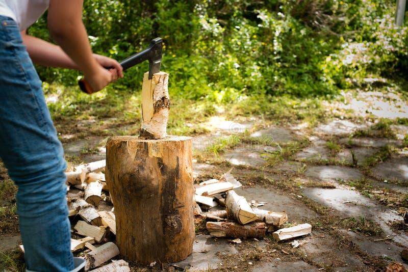 Νεαρός άνδρας με το τεμαχίζοντας ξύλο τσεκουριών σε έναν τεμαχίζοντας φραγμό στοκ φωτογραφίες