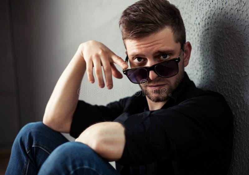 Νεαρός άνδρας μόδας που κρατά τα μοντέρνα γυαλιά ηλίου του σε γκρίζο στοκ φωτογραφία με δικαίωμα ελεύθερης χρήσης